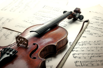 Old scratched violin with sheet music. Vintage style.