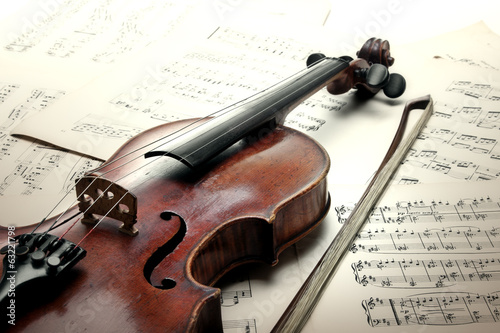 Staande foto Muziekwinkel Old scratched violin with sheet music. Vintage style.