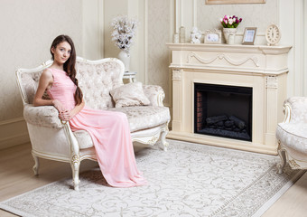 Young girl in elegant pink dress sitting on couch