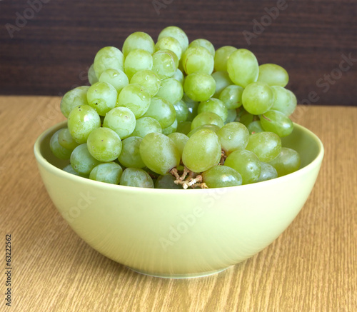 Grape on branch in green bowl on sandy brown wooden table