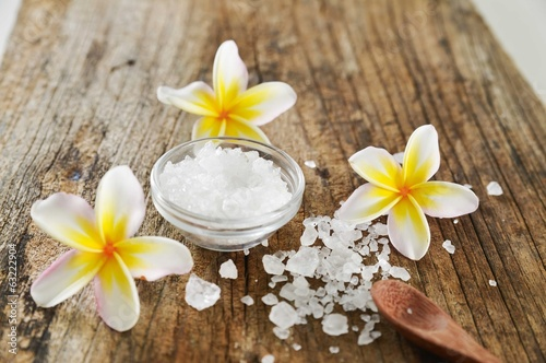 frangipani with many salt in bowl ,spoon on old wood background.