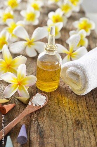 frangipani ,towel, oil, salt in spoon on old wood background