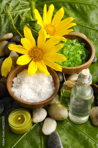 flower and stones with massage oil on green banana leaf