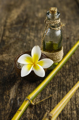 soap, frangipani in bowl and bamboo grove on old wood
