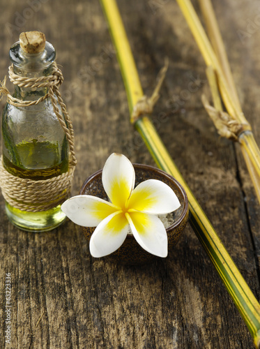 frangipani in bowl and dry bamboo grove on old wood