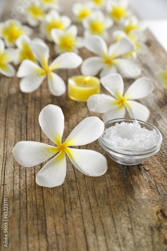 frangipani flowers with salt in bowl and driftwood texture