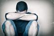 Sad youg man sitting on the floor crying
