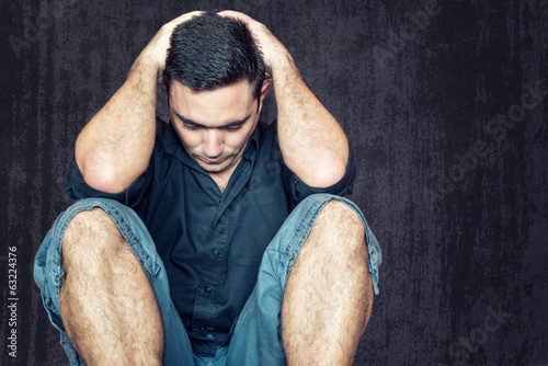 Sad and depressed young man sitting on the floor