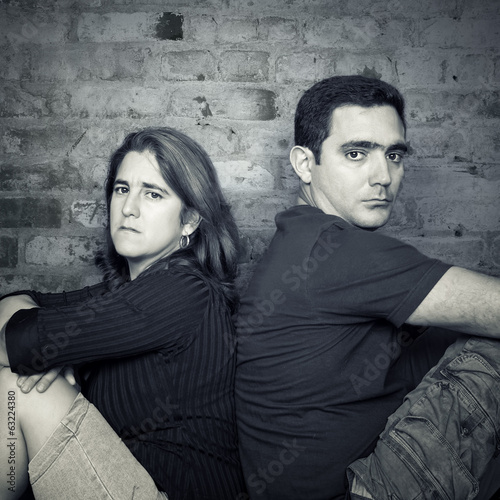 Young couple angry at each other sitting back to back
