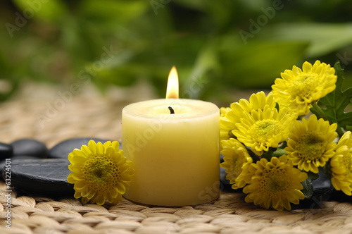 branch tropical flower and candle, stones on mat