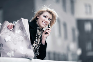 Young woman with shopping bags calling on the phone