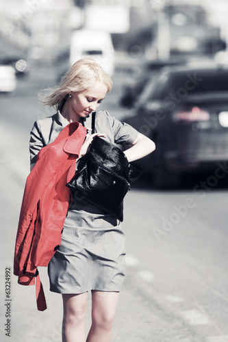 Young blond woman walking on a city street