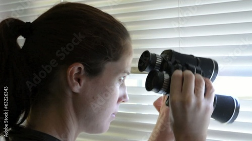 Young woman spy looks and searches with binoculars