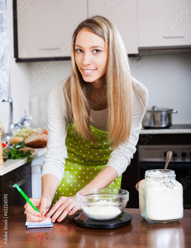 Housewife  weighing floor on kitchen scales