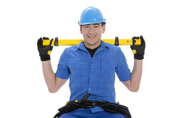 Handwerker lächelt mit Wasserwaage hinter dem Rücken