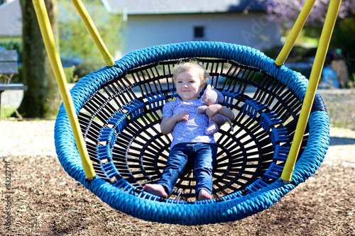 Cute toddler girl in casual outfit relaxing on a swing net