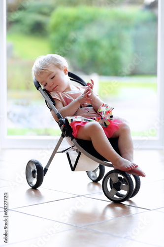 Cute toddler girl sleeping indoors in doll stroller toy