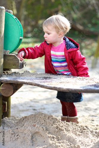 Toddler girl playing with sand in outdoor playground in the park