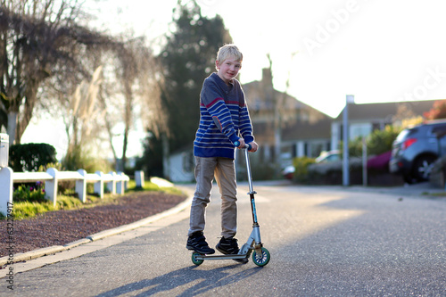 Happy boy with push scooter on the street