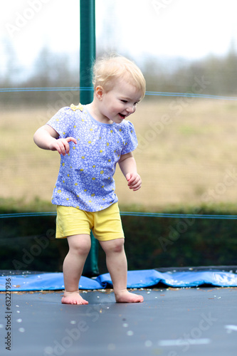 Happy toddler girl jumping on trampoline outdoors