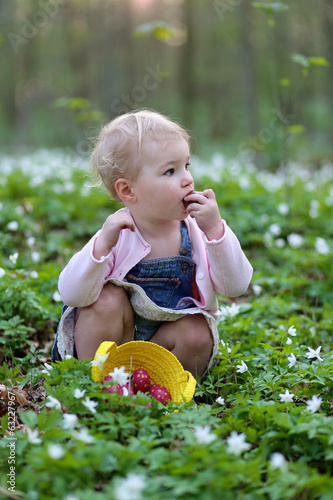 Happy toddler girl enjoying eggs hunting in the forest on Easter