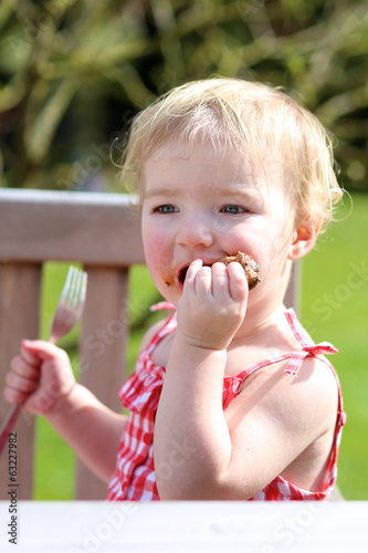 Funny toddler girl eating bbq meat outdoors in the garden