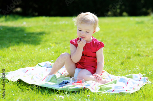 Happy toddler girl eating berries sitting in the garden