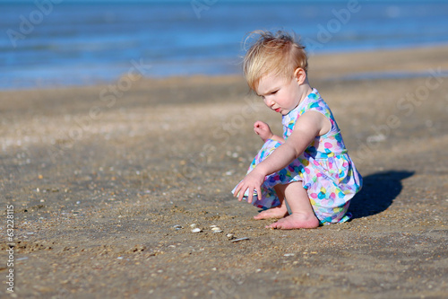 Cute toddler girl playing on the beach on summer day