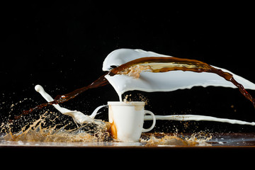 Coffee and milk pouring in a cup