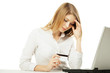 Shoked businesswoman with laptop and credit card