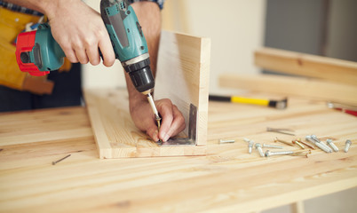 Close up of carpenter working with drill