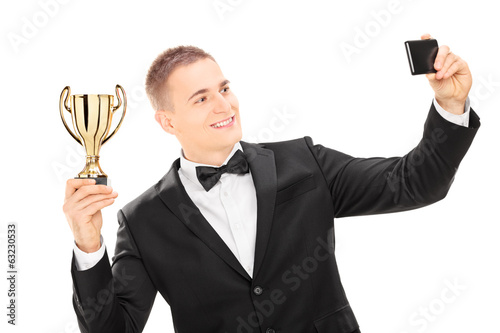 Elegant male holding trophy and taking a selfie