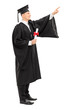 Male college graduate with a diploma pointing up