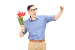 Man holding flowers and taking a selfie