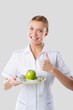 nutritionist holding hands green apple and measuring