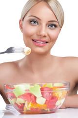 Beautiful woman eating fruit salad