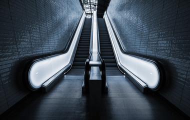 Perspective of two empty escalators with illuminated sides