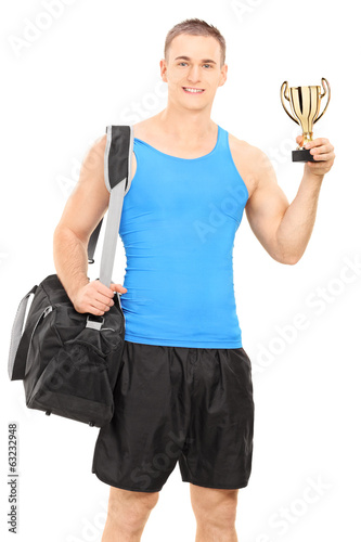 Young man with sports bag and a trophy