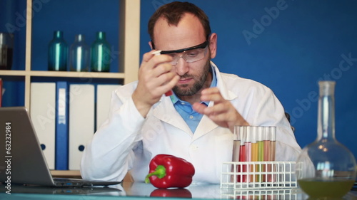 Biochemist inject chemicals in red pepper in laboratory