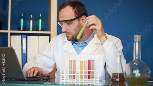 Scientist examine chemicals in test tubes, writing results on la