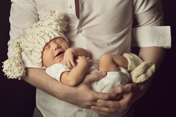 newborn baby boy smiling in woolen hat, sleeping on father hand