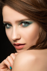Portrait of beautiful young woman with blue nails and eye makeup