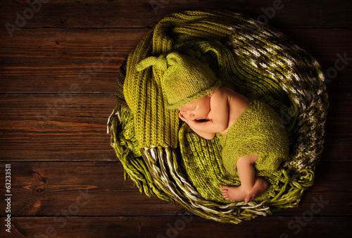 baby newborn portrait, kid sleeping in woolen hat on brown wood