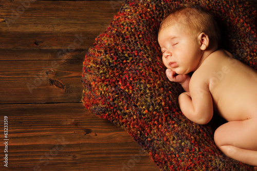 baby newborn portrait, kid sleeping in woolen blanket on brown