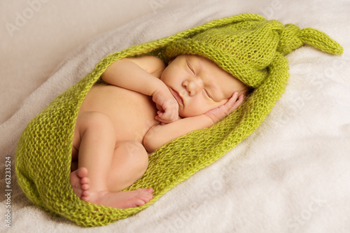 baby newborn portrait, kid sleeping in green woolen blanket