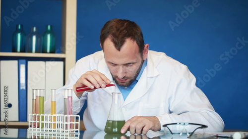 Scientist pouring chemicals into erlenmeyer flask