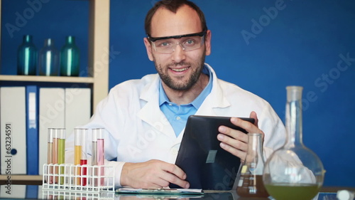 Portrait of young happy scientist with tablet computer in labora