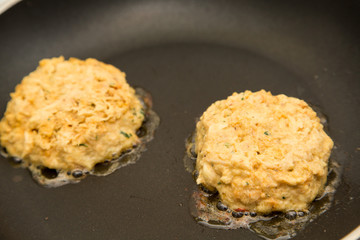 Two Fresh Crab Cakes Cooking in Oil