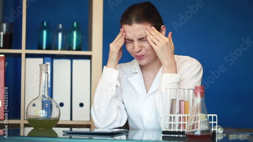 Female scientist having headache during work in laboratory