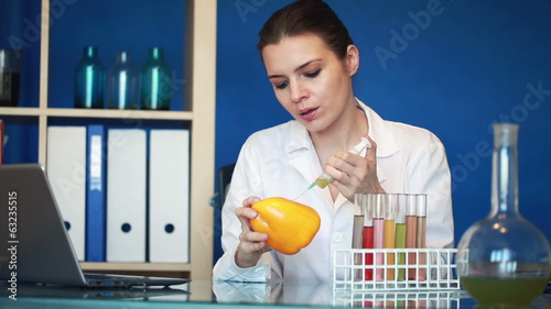 Female biochemist injecting substance into yellow pepper